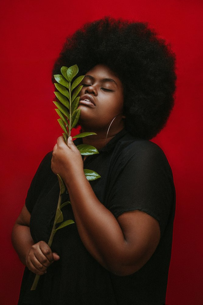 Why Black Mental Health Matters Now More Than Ever (image of a beautiful Black woman with a gorgeous afro. She is holding a plant next to her face and her eyes are closed. She is photographed with a dark red background)