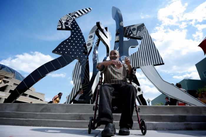 The Wright Museum shares heartwarming message on the passing of Detroit artist Charles McGee. Photo of the artist Charles McGee in front of the United We Stand Sculpture he created.