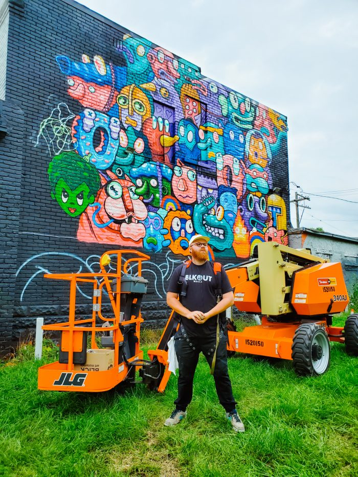 """Mississippi artist Birdcap stands in front of his mural """"Freestyle Congregation"""" located at 952 Clay St., Detroit. BLKOUT Walls Mural Festival"""