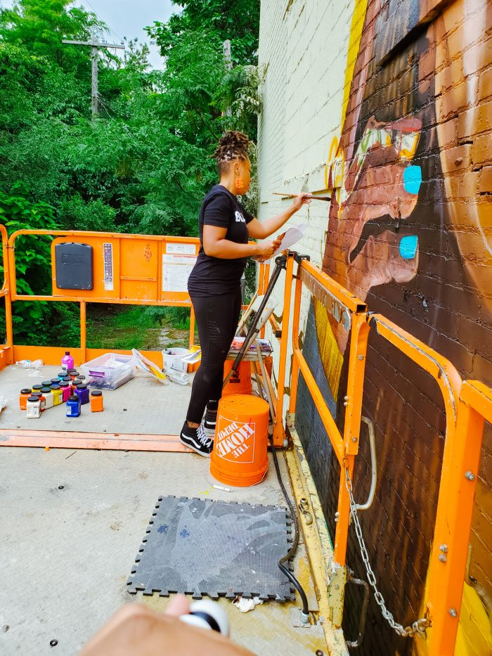 Sydney G. James paints her mural portrait of Yolanda Williams at the BLKOUT Walls Mural Festival in Detroit's North End neighborhood.