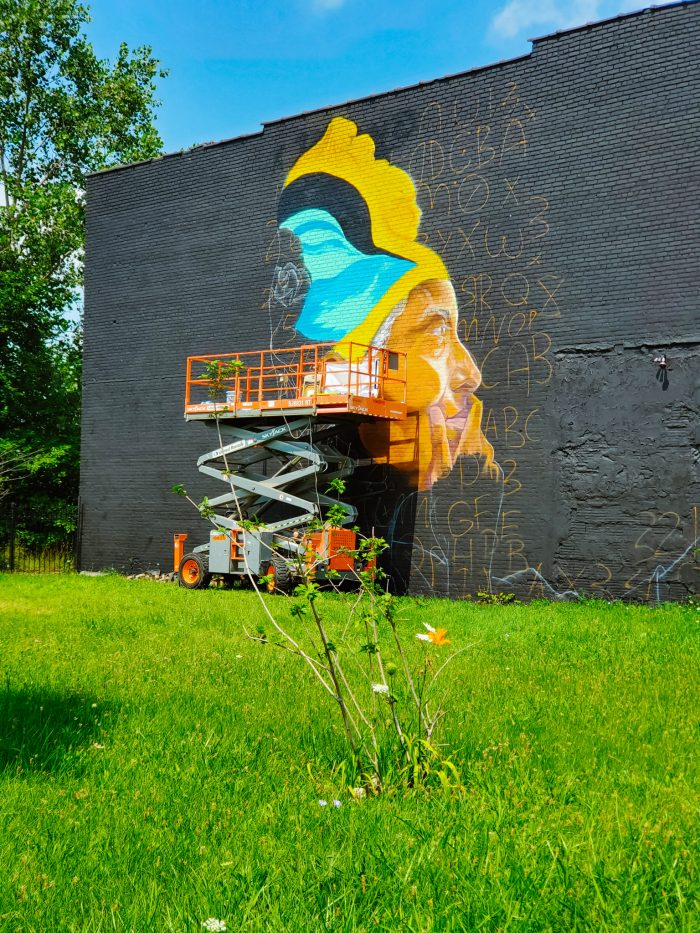 """BLKOUT Walls Mural Festival 2021 was co-created by Sydney G. James, Max Sansing, and Thomas """"Detour303"""" Evans. Mural featured is  a work in progress art piece by Sydney G. James"""