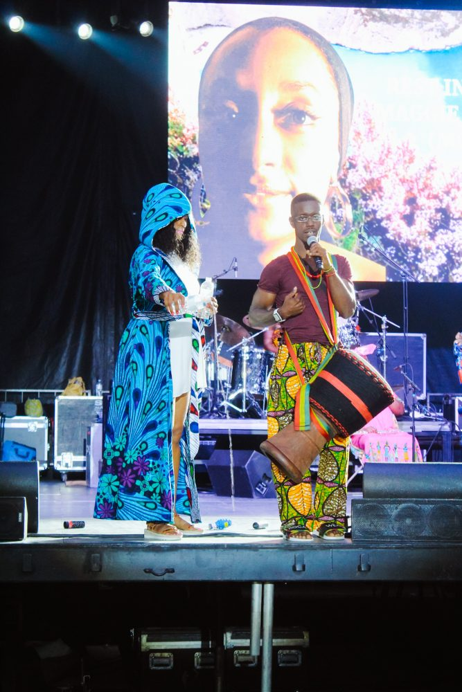 Piper Carter pours water onto the ground during the libation ceremony at the African World Festival. Sowande Keita stands beside her speaking to the audience on a microphone.