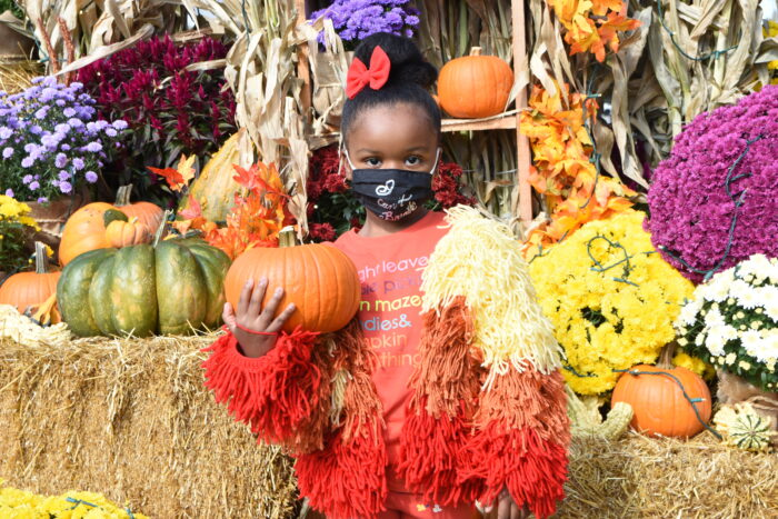 A little girl poses with a pumpkin at Cider in the City, a fall event at Beacon Park in Downtown Detroit.