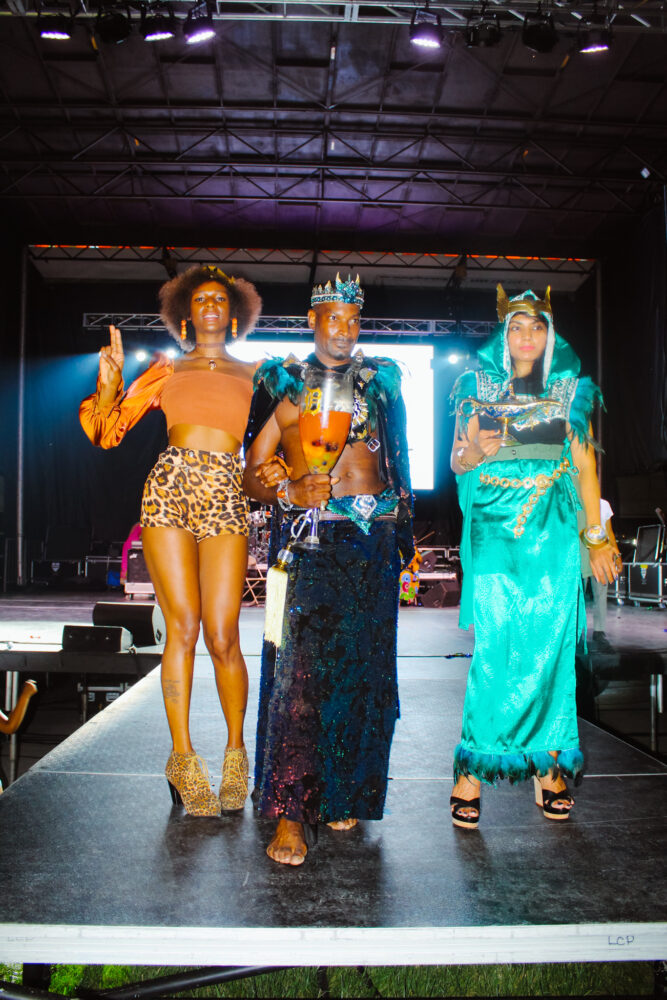 Sevin McClure, designer of The McClure Collection, poses with two models wearing his fashion designs. (Detroit, Michigan)